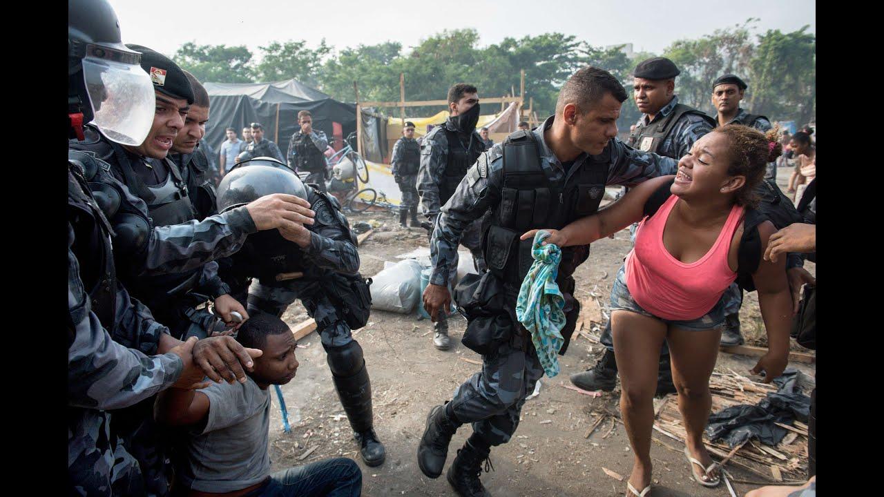 Policiais desocupando moradias ilegais, com o uso da força. Créditos: Revista IstoÉ via Youtube
